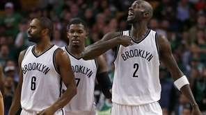 Nets center Kevin Garnett argues as he and