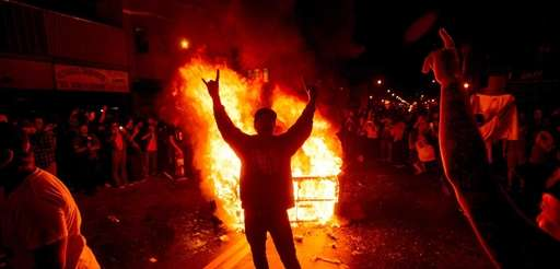 A man celebrates in front of a burning