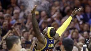 Cleveland Cavaliers' LeBron James tosses chalk in the