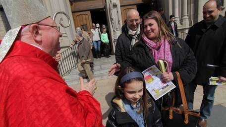 Bishop William F. Murphy greets worshippers after Palm