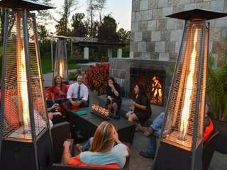 Guests socialize by the outdoor fireplace and heat