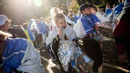 A runner opens a bottle of water after