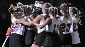 Garden City's Emily Clarke, left, and teammates celebrate