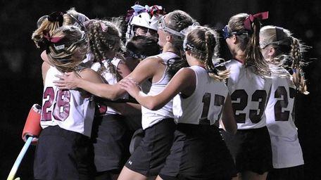 Garden City's Emily Clarke, left, and teammates celebrate