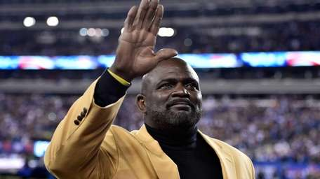 Former New York Giants player Lawrence Taylor waves