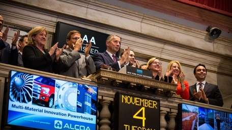 Klaus Kleinfled, center, CEO of Alcoa, rings the