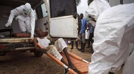 Healthcare workers load a man suspected of suffering