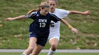 Shoreham-Wading River's Alex Kuhnle dribbles around Sayville's Kaitlyn