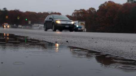 Cars move as rain falls along Sills Road