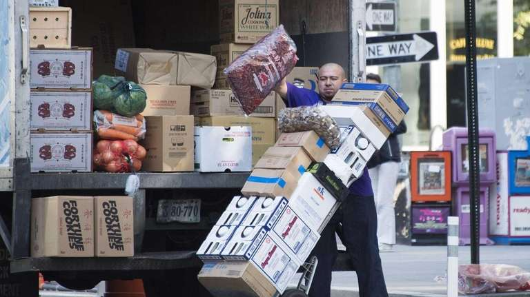 A worker unloads grocery goods in Washington, D.C.,