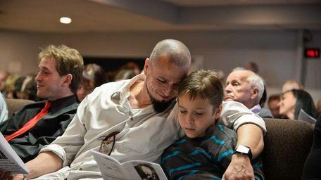 James E. Tilden sits with his son Vincent,