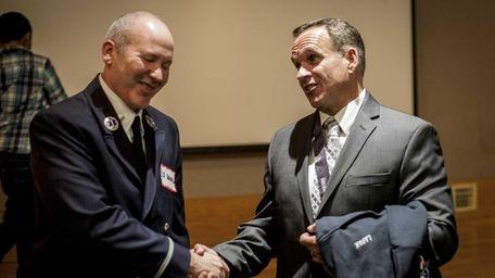 Chris LaPak, 52, of Copiague, right, shakes hands