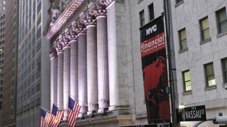 A street sign for Wall Street hangs near