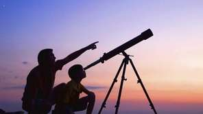 A young boy looking thru a telescope at