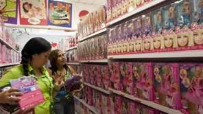 Shoppers look at the selection of Barbie dolls