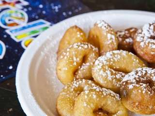 Freshly made mini doughnuts are sprinkled with powdered
