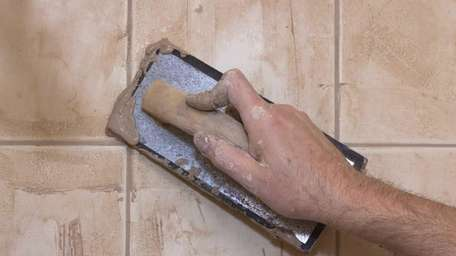 Man's hand with trowel while grouting ceramic tile.