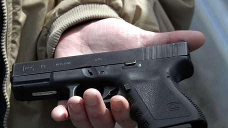 A firearms owner displays a Glock 9-mm pistol