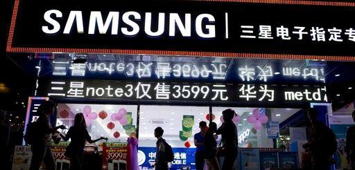 Pedestrians walk past Samsung Electronics Co. signage displayed