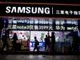 Pedestrians walk past Samsung Electronics Co. signage displayed