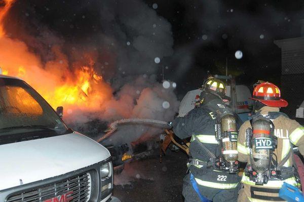 Firefighters hose down a fire in East Farmingdale