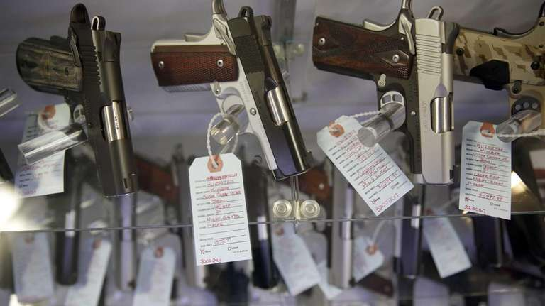 Handguns sit in a glass display case at