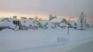 Snow covers a street at daybreak Wednesday, Nov.