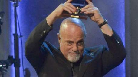 Billy Joel holds up his 2014 Gershwin Prize