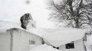A man shovels his roof as snow continues