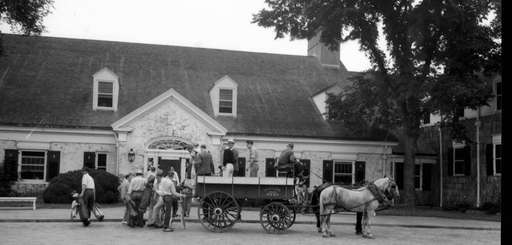 Historic photo of golfers in horsing carriages arriving
