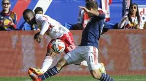 New England Revolution forward Kelyn Rowe blocks a