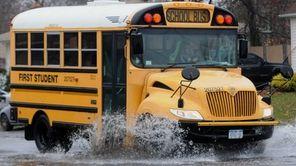 A school bus navigates through a large puddle
