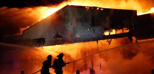 Firefighters work to extinguish a raging fire on
