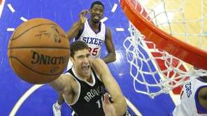 Brooklyn Nets' Brook Lopez shoots with Philadelphia 76ers'