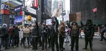 Demonstrators stand in Times Square during the Macy's