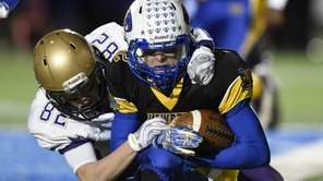 Sayville's Kevin Murphy tackles Lawrence quarterback Sean Moran