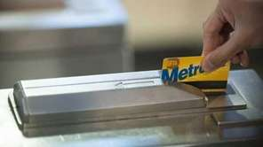 A subway rider swipes a MetroCard at a
