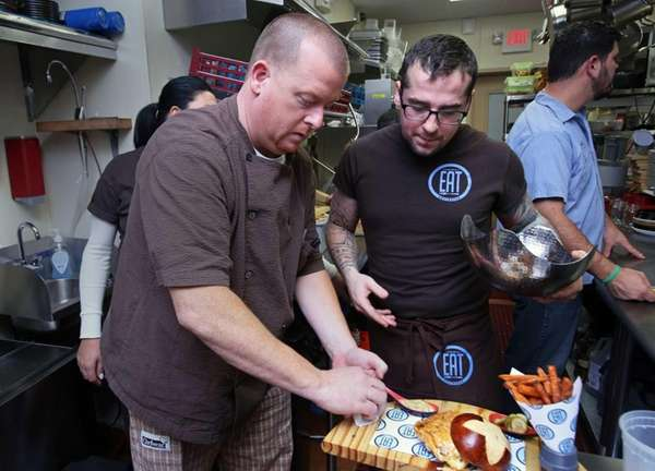 Chef John Maher, left, plates food in the