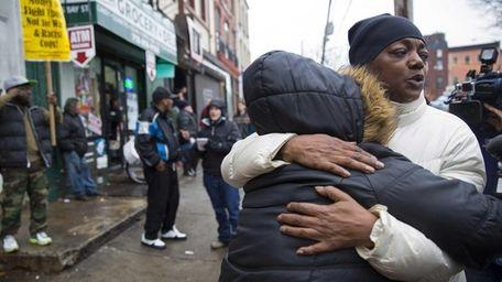 People embrace on Wednesday, Dec. 3, 2014, near