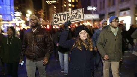Demonstrators march in Times Square late Wednesday, Dec.