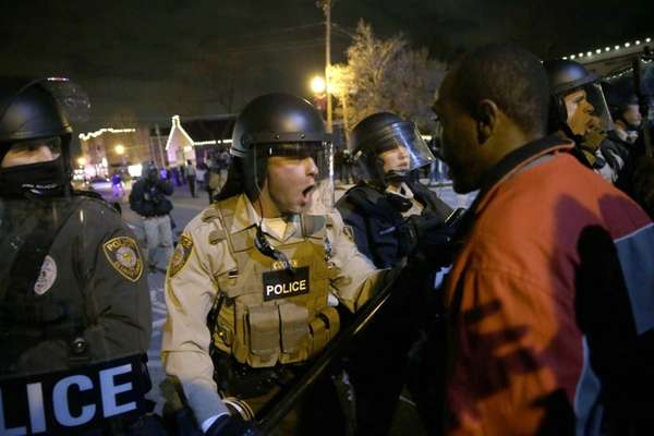 Police officers confront protesters after the announcement of