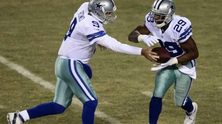 Dallas Cowboys quarterback Tony Romo hands off the