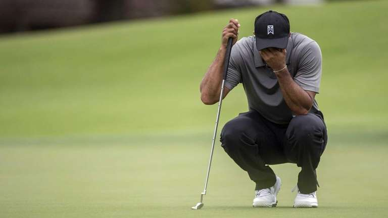 Tiger Woods covers his face as he waits