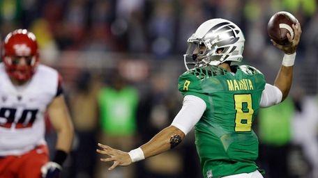 Oregon's Marcus Mariota, right, passes against Arizona during