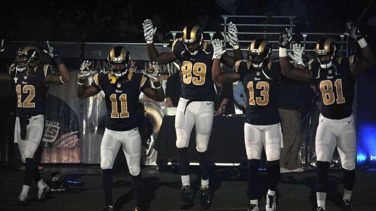 Members of the St. Louis Rams raise their