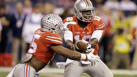 Ohio State quarterback Cardale Jones, right, hands off