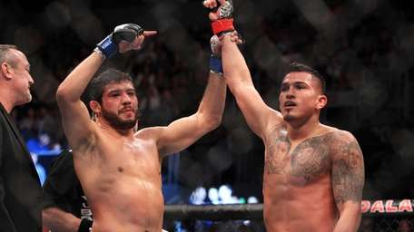 Anthony Pettis, right, has his hand raised by