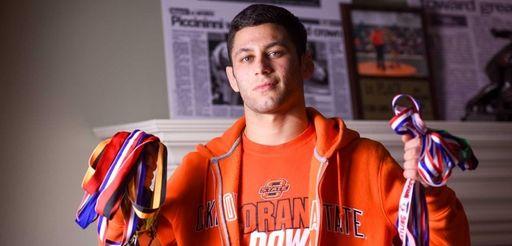 Ward Melville senior wrestler Nick Piccininni holds up
