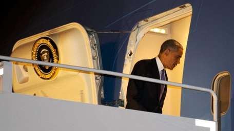 President Barack Obama boards Air Force One in