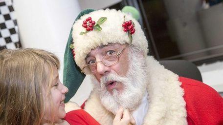 Emily Tell, 8, of Elmont, pulls Santa's beard.